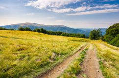 Road through grassy meadow in mountains. Beautiful summer landscape of Carpathians. Apetska mountain in the distance under the cloudy sky Royalty Free Stock Photos