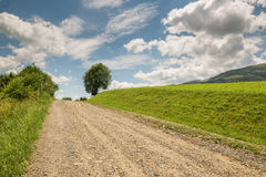 Road with gravel stretches up the hill Stock Photography