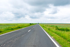 Road through the green field Royalty Free Stock Photo