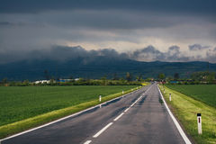 Road through the green field with mountain on background Royalty Free Stock Images