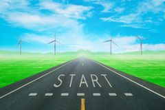 Road through the green field with sign start on asphalt Stock Image