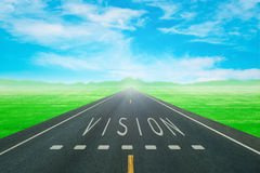 Road through the green field with sign vision on asphalt Royalty Free Stock Image