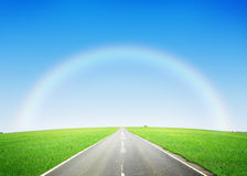 Road through the green field and sky with rainbow Royalty Free Stock Photos