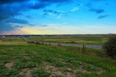 Road through green fields. Beautiful bly sky Royalty Free Stock Images