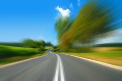 Road among green fields with motion blur effect. Blue sky in the background stock photo