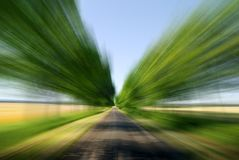 Road among green fields with motion blur effect. Blue sky in the background royalty free stock images