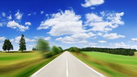Road among green fields with motion blur effect. Blue sky and white clouds in the background stock photography