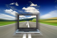 Road among green fields with motion blur effect. And laptop, blue sky in the background royalty free stock photography