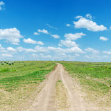Road in green grass and blue sky Royalty Free Stock Images