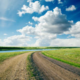 Road in green grass and cloudy sky Royalty Free Stock Photos