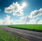 Road in green grass and sky with sun Royalty Free Stock Images