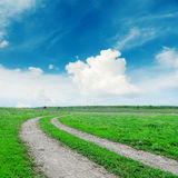 Road in green grass under blue sky Stock Images