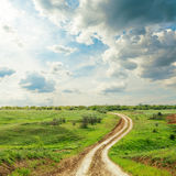 Road in green meadow and dramatic sky Royalty Free Stock Photo