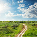 Road in green meadow under clouds in blue sky. In sunset Royalty Free Stock Photo