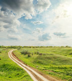 Road in green meadow under clouds in sunset Royalty Free Stock Image