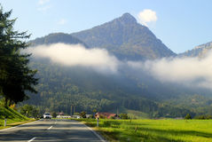 The road between green meadows with the mountains in the clouds on the background in the sunny day. Royalty Free Stock Photos