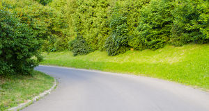 The bend of the road. The road passes nearby bushes and trees Stock Photography