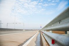Road with guard rail. Barrier, guard rail, designed to prevent the exit of the vehicle from the curb or bridge, moving across the dividing strip royalty free stock photos