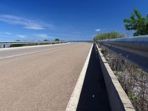 Road and guardrail. Empty road with guardrail and blue sky with white clouds royalty free stock photo