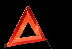 Road hazard warning triangle. Isolated on a black background Stock Photos