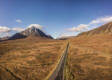 Road heading through autumn valley with beautiful mountain aerial view