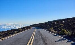 Road heading down from the Haleakala mountains with a view of clouds on the horizon. A road heading down from the Haleakala mountains with a view of clouds on stock photography