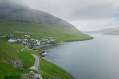 A road heading to Faroese village of Bour on a cold and cloudy day. Green grass on steep cliffs and ocean fjord