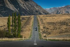 Road heading into the valley in New Zealand stock images