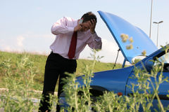 Road help. Businessman on a mobile phone in front of a broken car royalty free stock images