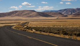 Road through high desert of eastern Oregon. Paved road winds through the valley in the high desert of eastern Oregon at the Steens Mountains royalty free stock image