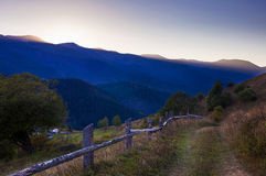 The road on hill and fence on mountain background Royalty Free Stock Image