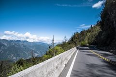 Road on the hill side running through forest with mountains, blue sky, and clouds. stock photo