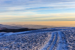 Road on hill in winter in Carpathians Stock Images