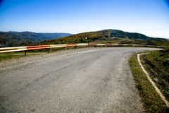 Road On Hills. Road with guardrails winding through a hilly area Stock Photo