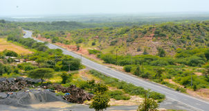Road through hills and green trees. Kutch Stock Photos
