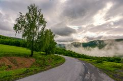 Road through hillside on foggy morning. Beautiful countryside landscape of Carpathian region Stock Photography
