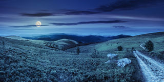 Road on hillside meadow in mountain panorama at night Stock Images