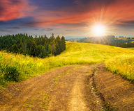 Road on hillside meadow in mountain at sunset Royalty Free Stock Photos