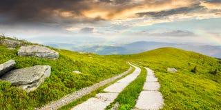 Road on a hillside near mountain peak Royalty Free Stock Image