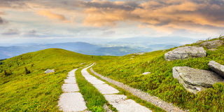 Road on a hillside near mountain peak at sunrise Royalty Free Stock Images