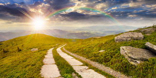 Road on a hillside near mountain peak at sunset Stock Images