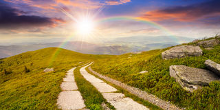 Road on a hillside near mountain peak at sunset royalty free stock photos