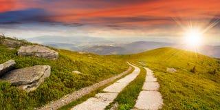 Road on a hillside near mountain peak at sunset Royalty Free Stock Photo
