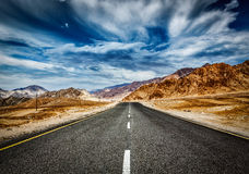 Road  in Himalayas with mountains. Travel forward concept background - road in Himalayas mountains and dramatic clouds. Ladakh, Jammu and Kashmir, India Royalty Free Stock Image