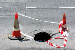 Road hole with warning cones. And tape Royalty Free Stock Photo