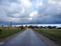 Road, homes and beautiful cloudy sky, Lithuania stock photos