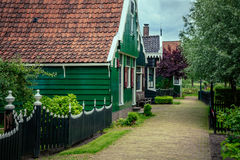 Road between the houses. The road between the old green country houses stock images