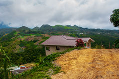The road and houses in the village on the slopes of the mountains with clouds. Sabah, Borneo, Malaysia Royalty Free Stock Photos