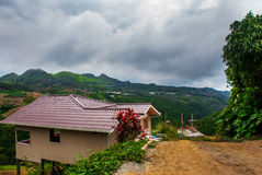 The road and houses in the village on the slopes of the mountains with clouds. Sabah, Borneo, Malaysia Royalty Free Stock Images