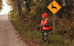 Road hunter. Hunter standing by a deer crossing sign waiting for game Royalty Free Stock Photography